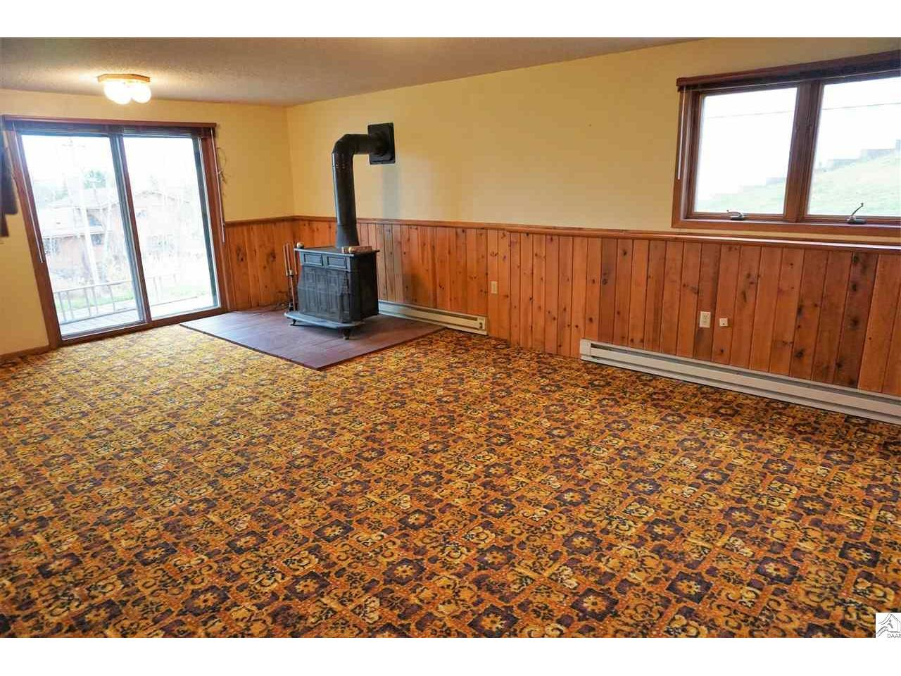 Large Family Room with Patio Doors out and Freestanding Wood Burner.