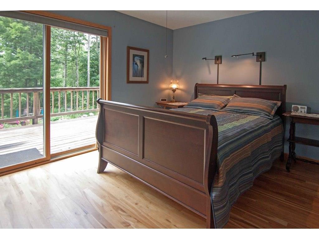 Main floor bedroom with slider to deck overlooking pond.