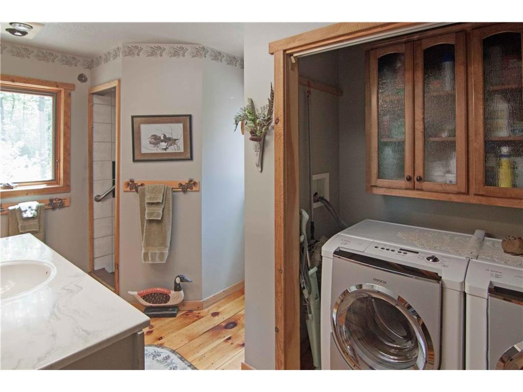 Main floor bath and laundry with wood flooring, tiled shower.