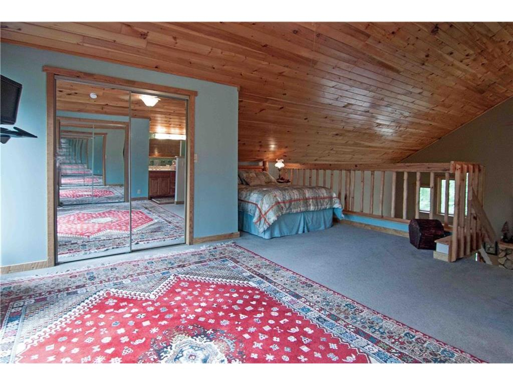 Loft bedroom with carpeted floors and plenty of storage space and master bath.