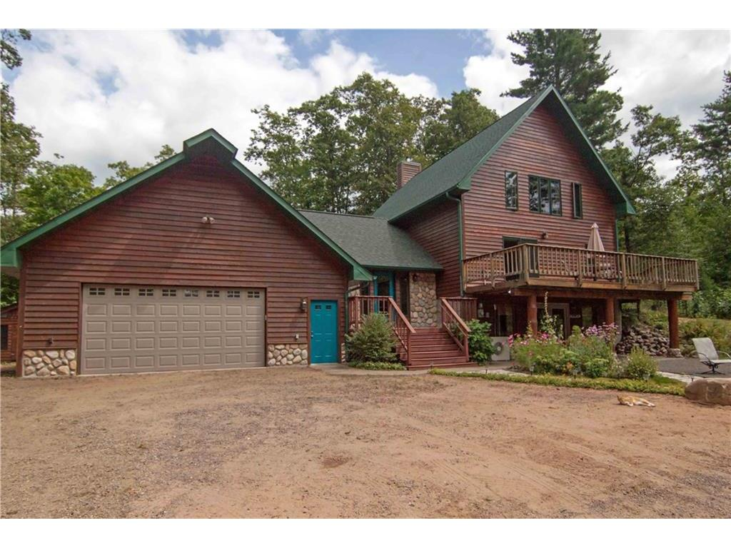 Attached 2 car garage, exterior front of home has large deck overlooking pond.