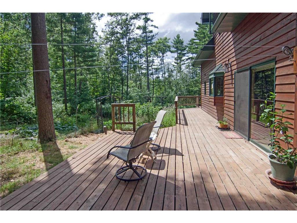 Back yard decking that wraps around to front. View of wooded acre and side yard with garden.