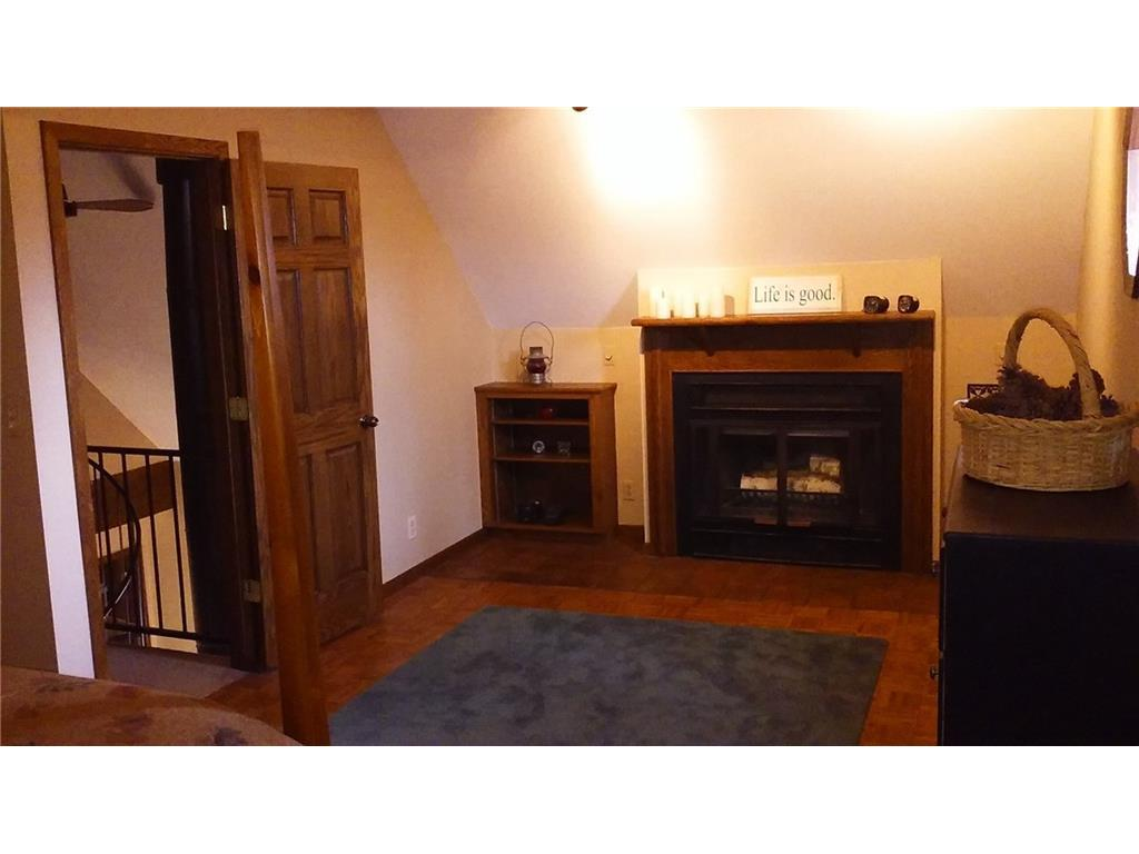 The other end of the larger upstairs bedroom with woodburning fireplace.