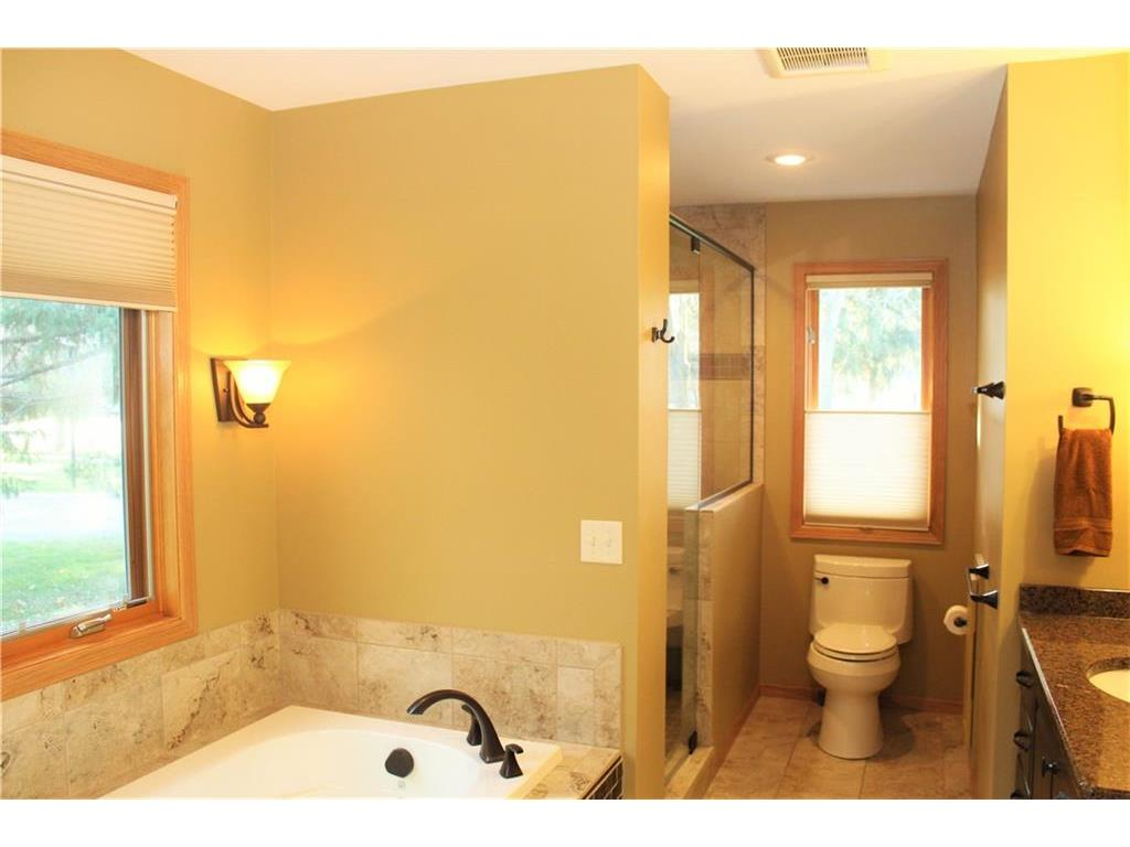 Remodeled & expanded master bath with in-floor heat and tiled step-in shower.