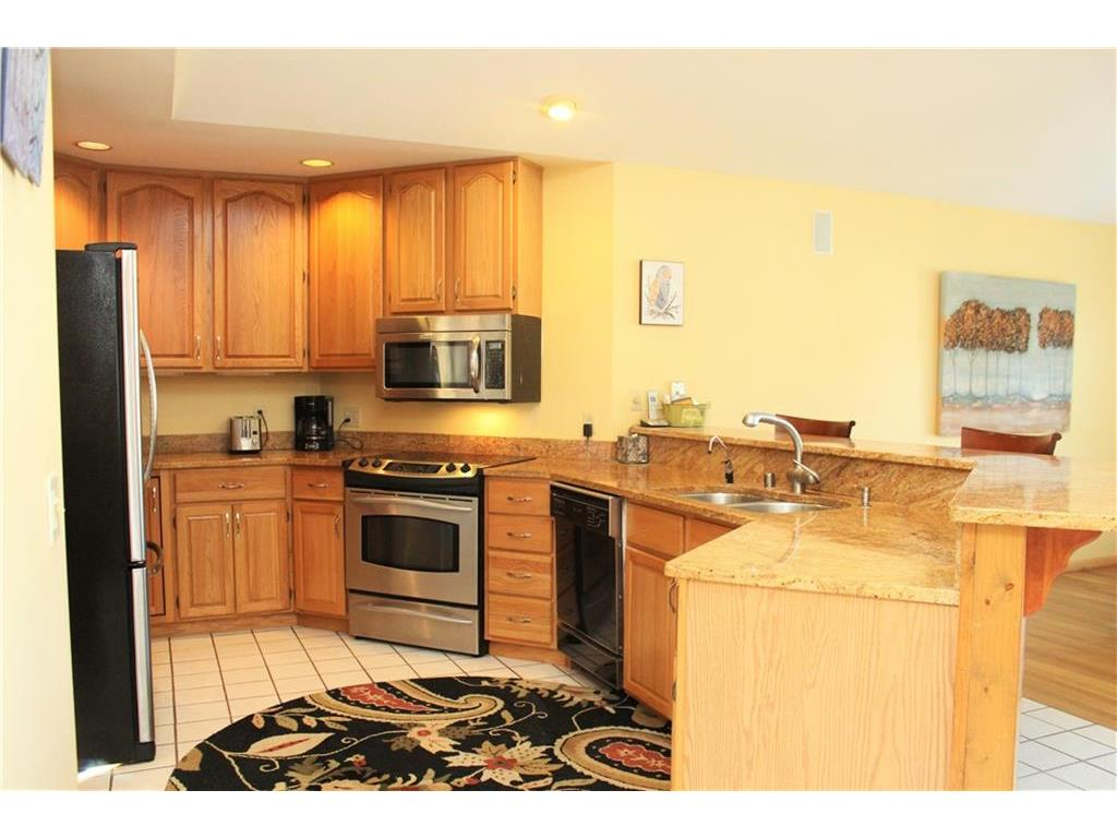Kitchen with sleek granite countertops and new stainless steel appliances