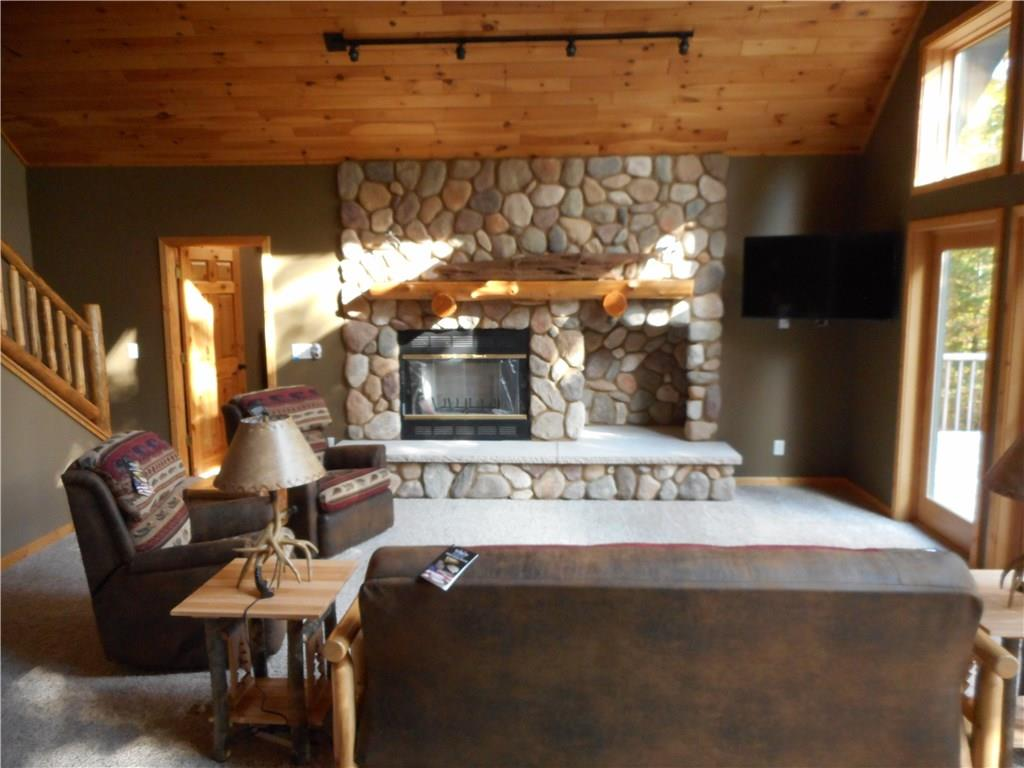 Living room with wood burning fireplace, walk out slider to composite decking.