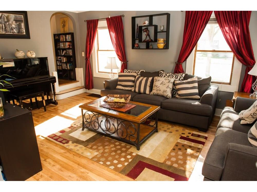 Sun-filled living room with beautiful re-finished hardwood flooring, plus charming curved archway to stairs.