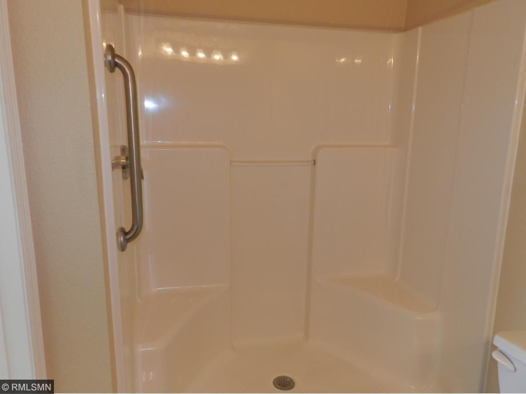 Master bath with a large walk in shower with grab bars and sitting benches.