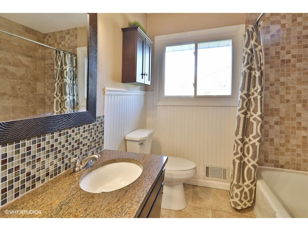 Wonderfully updated bathroom with tiled floors, backsplash and shower/tub! The bead-board walls add additional character and warmth!