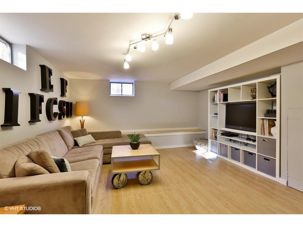 Large family room just recently redone featuring built-in storage bench and luxury vinyl flooring! There is also lots of additional storage space and/or work/hobby space!
