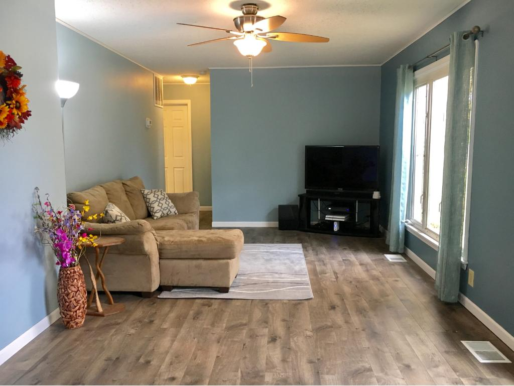 Bright and cheery living room with new floors and  fresh paint