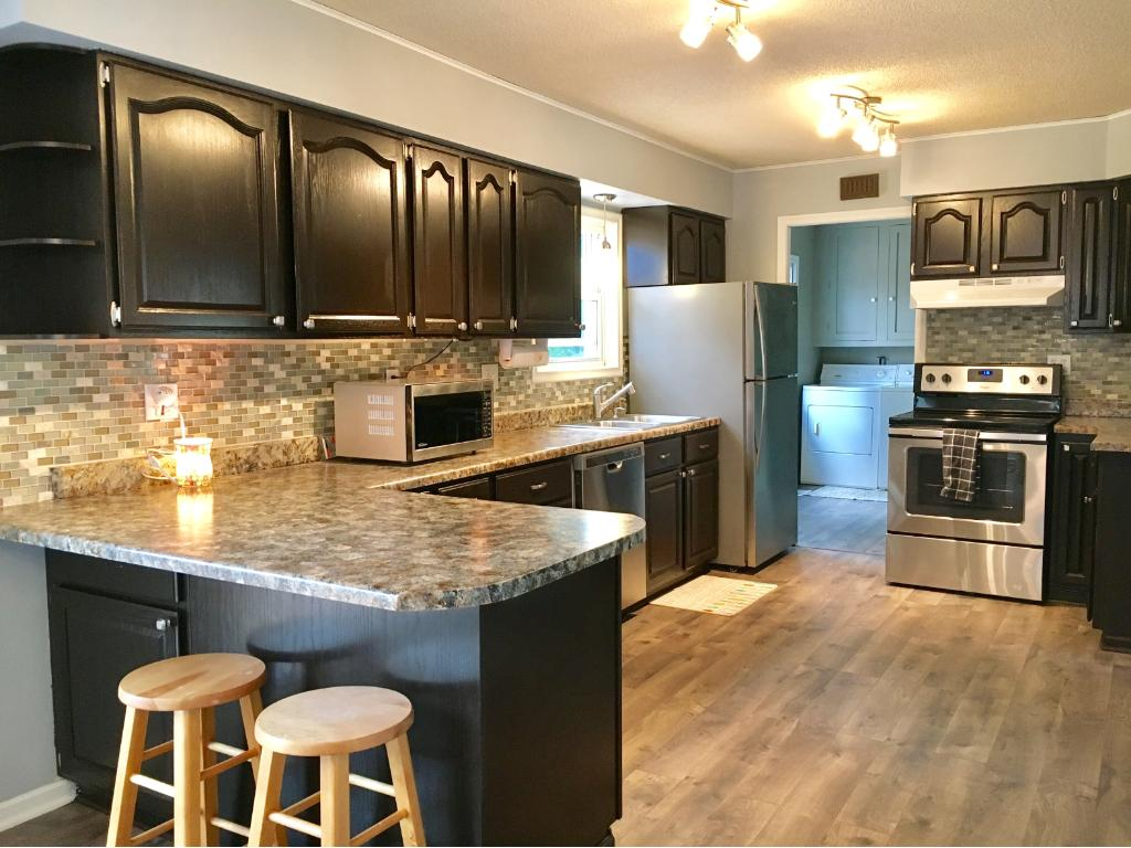 Spacious and functional kitchen with all new stainless steel appliances, floors, tiled back splash and light fixtures