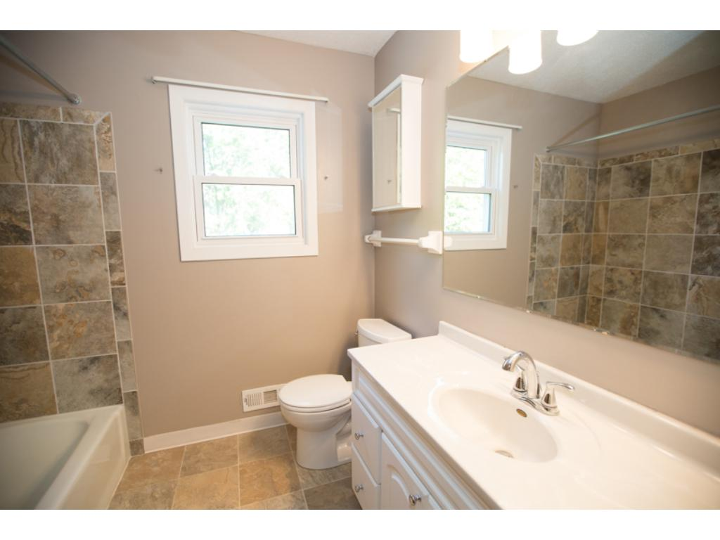 Updated bath with new vanity and tile shower surround.