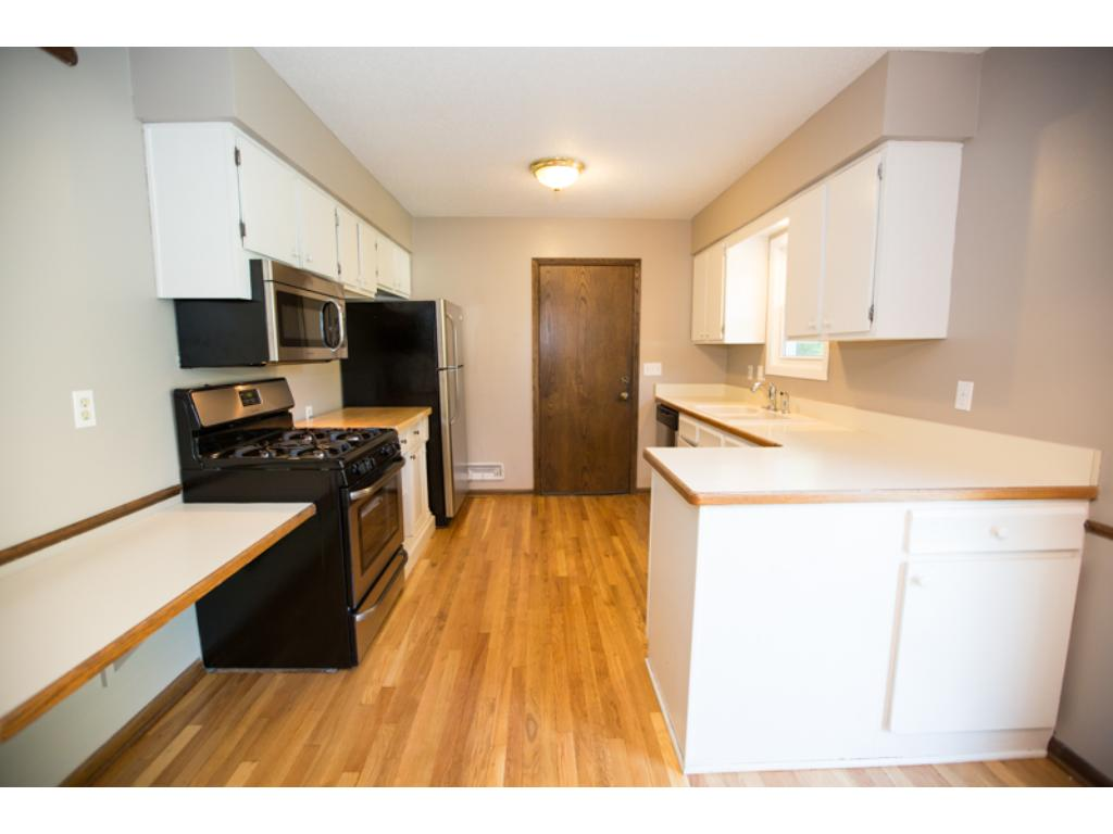 Kitchen with recently refinished  hardwood floors and new stainless steel appliances.