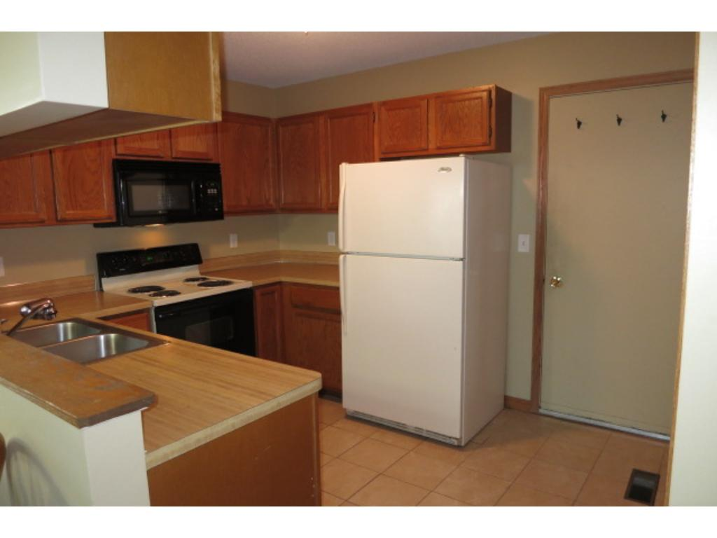 Enter into the kitchen from the garage which has shelving and extra storage options.