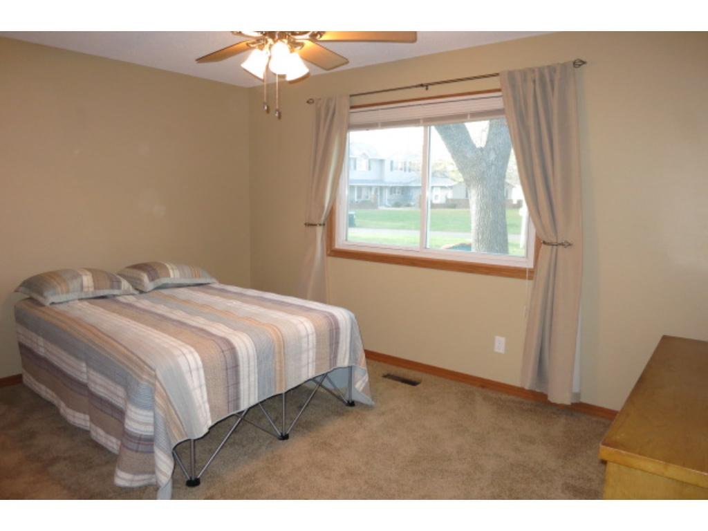 Nicely sized main bedroom with newer carpeting, a ceiling fan and a large closet.