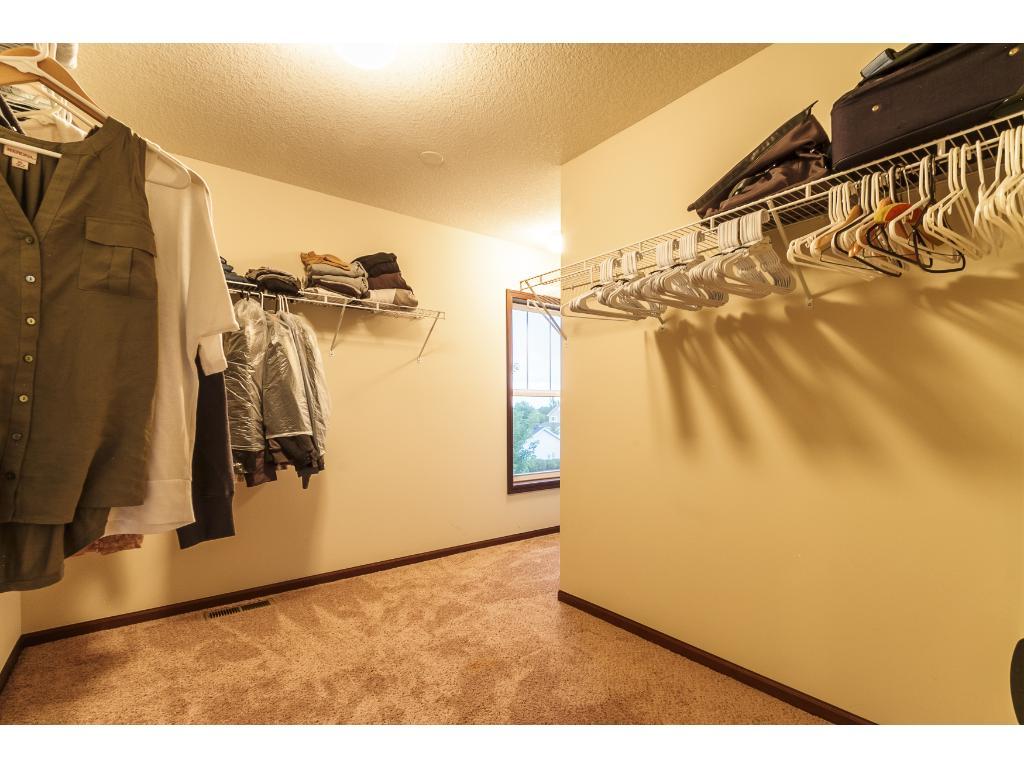 Huge walk-in closet with vanity area and window.