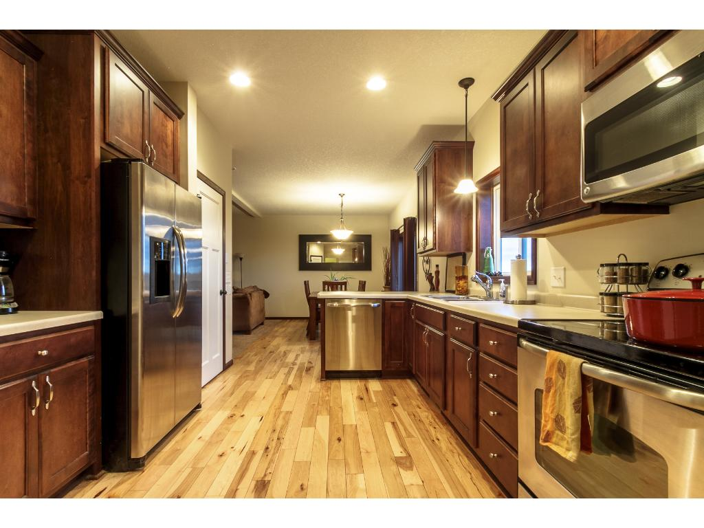 Kitchen features SS appliances and hickory hardwood floors.