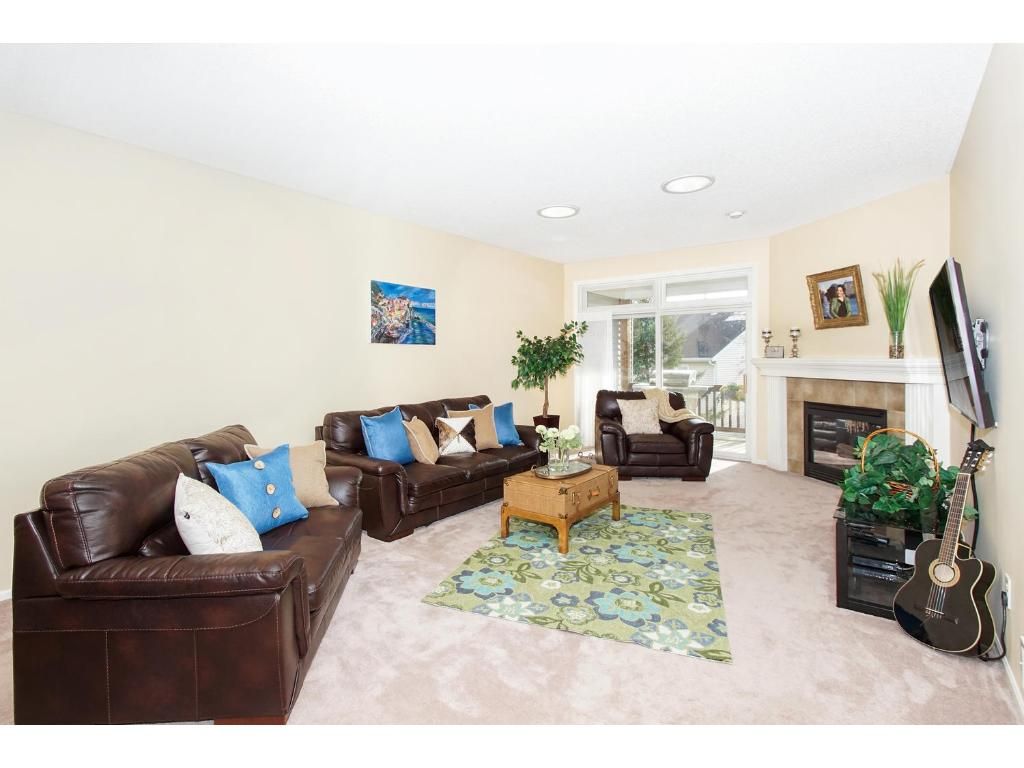 This great space has tall ceilings, carpet, sliding glass doors and sky lights inviting lots of natural light in. Beautiful gas burning fireplace with stone surround and a white mantle. Walk out the glass door to enjoy your private deck.