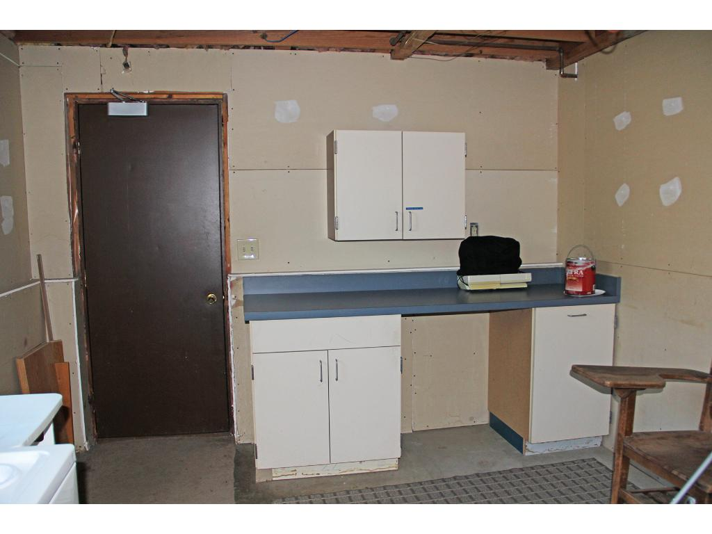 Workshop area in the lower level laundry/utility room with an access door to the attached garage.