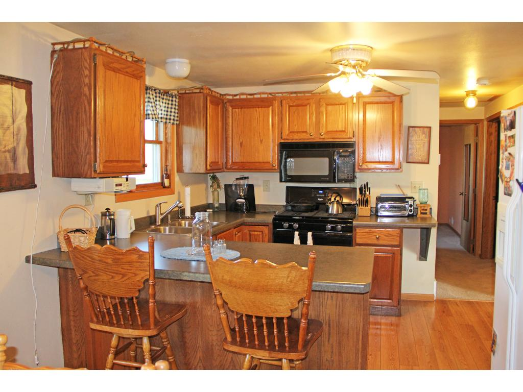 Kitchen with hardwood floors, eat around counter, open to the dining area.