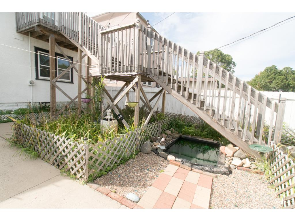 Pond surrounded by flowers, back stairs lead to master bedroom.