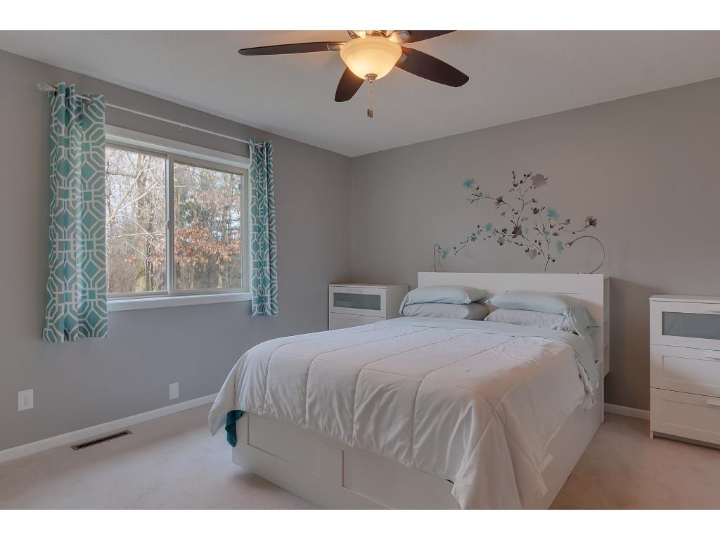 Enjoy a spacious master bedroom with a ceiling light fan fixture and carpet flooring. The window treatments throughout the home can stay.