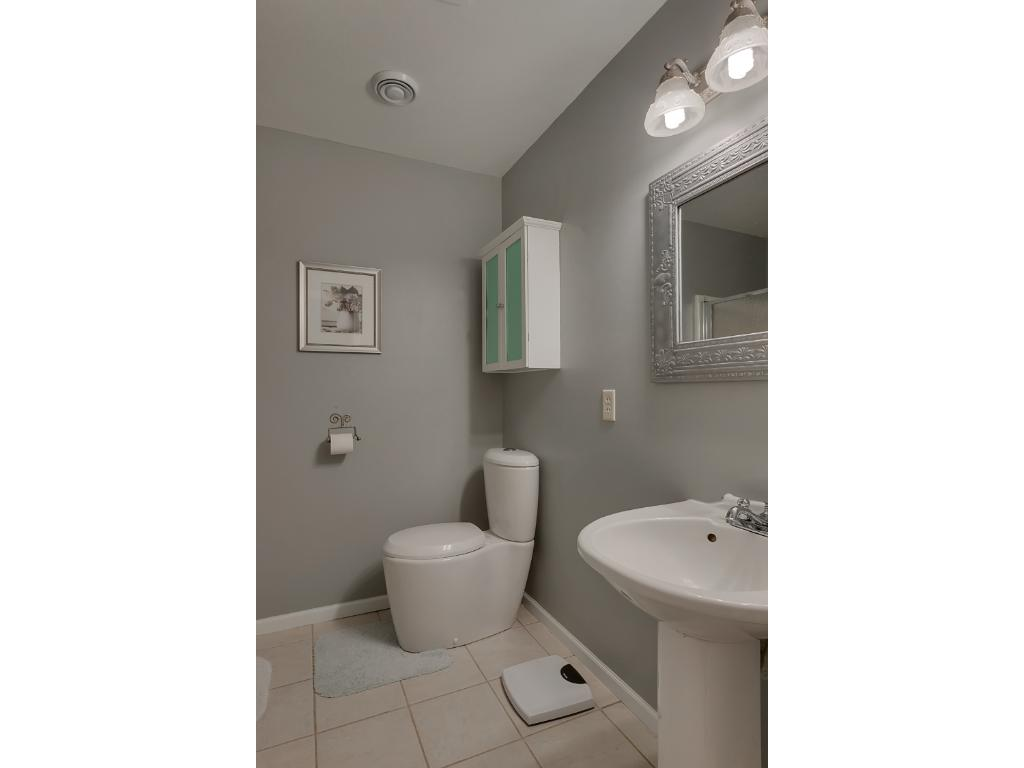 Here we see the 3/4 master bath with a pedestal sink, easy clean toilet stool and ceramic tiled flooring.