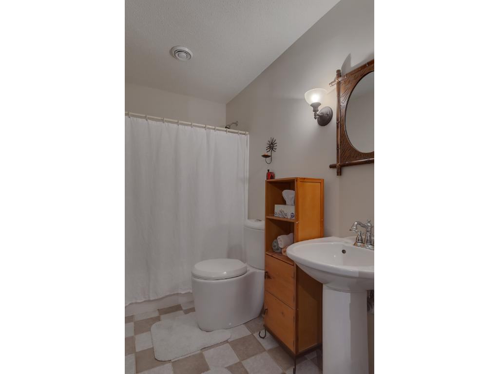 Here's the main level full bath.  It features a pedestal sink, full shower and ceramic tiled flooring.