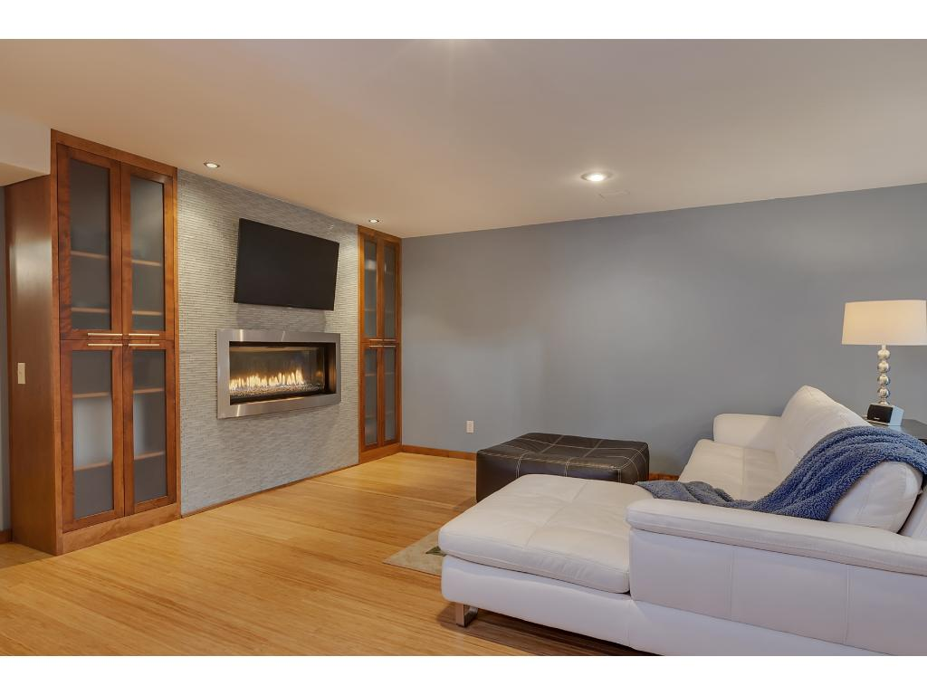This is a beautiful family room hosts a gorgeous gas fireplace with built-in cabinets on both sides and tiled surround.