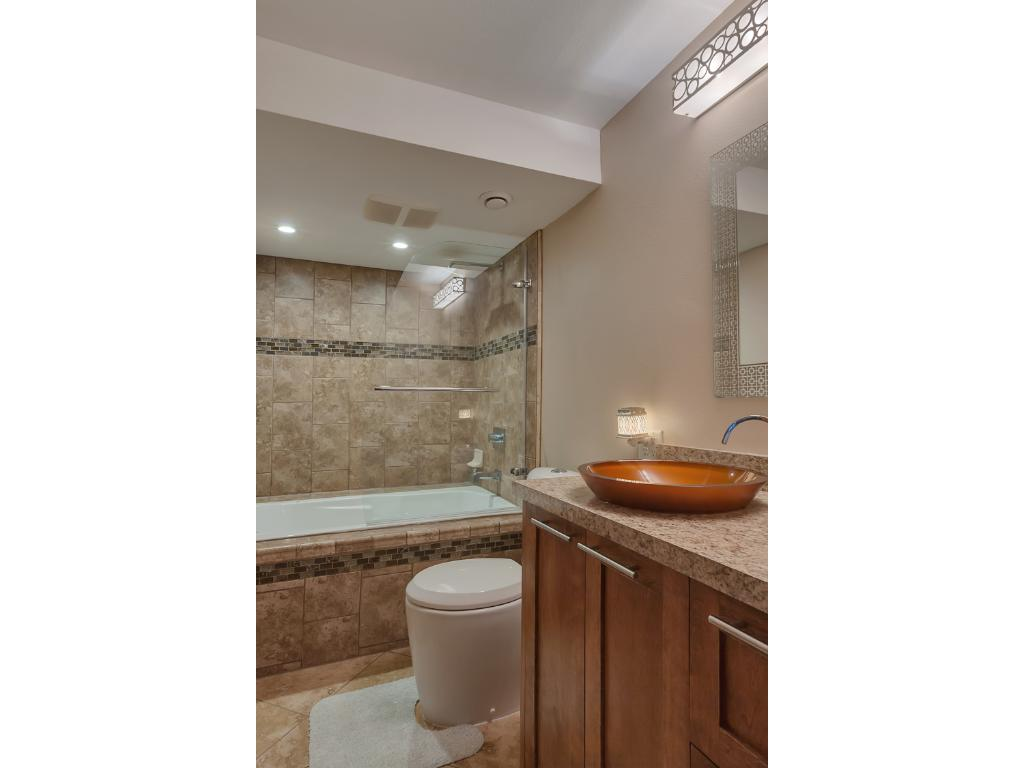 The lower level full bath has travertine heated flooring, fully tiled tub surround and a custom glass shower divider, custom built vanity, easy clean toilet stool, high end vessel sink, faucet & wall mirror.