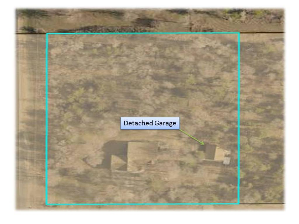 Aerial of the 2.5 acre wooded lot. The detached garage has a separate driveway.