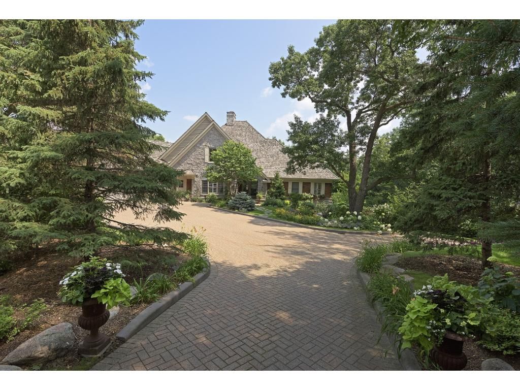 An Executive Setting on an acre lot with long herringbone paved driveway and a back drop of lush, mature trees in the beautiful Bell Oaks neighborhood of Eden Prairie.