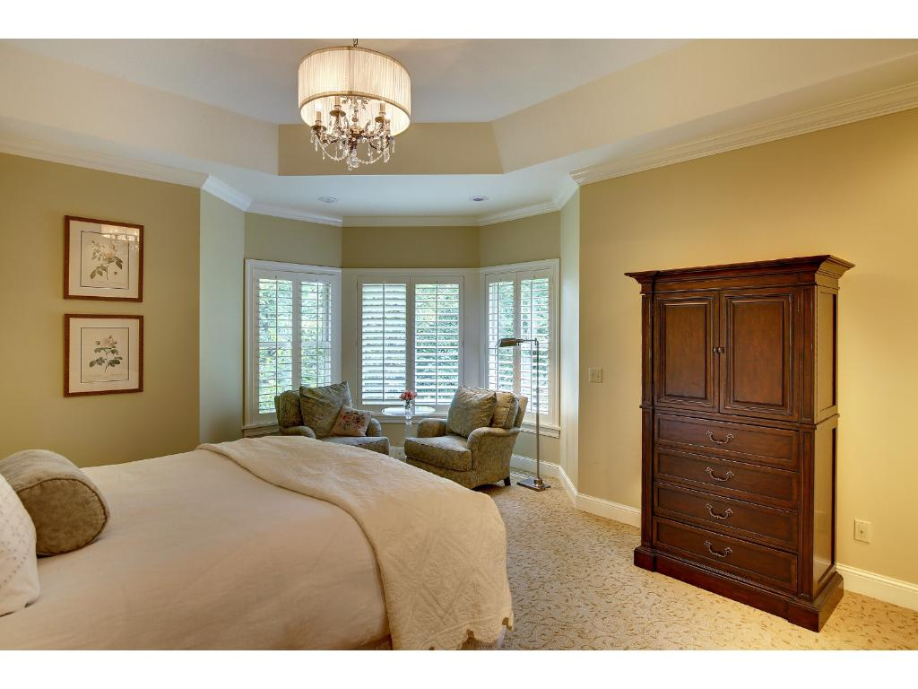 The Main Floor Master provides a serene Suite with a Tray Ceiling and sitting area with tree-top views. The spacious walk-in closet features wood floors and a custom California Closet system.