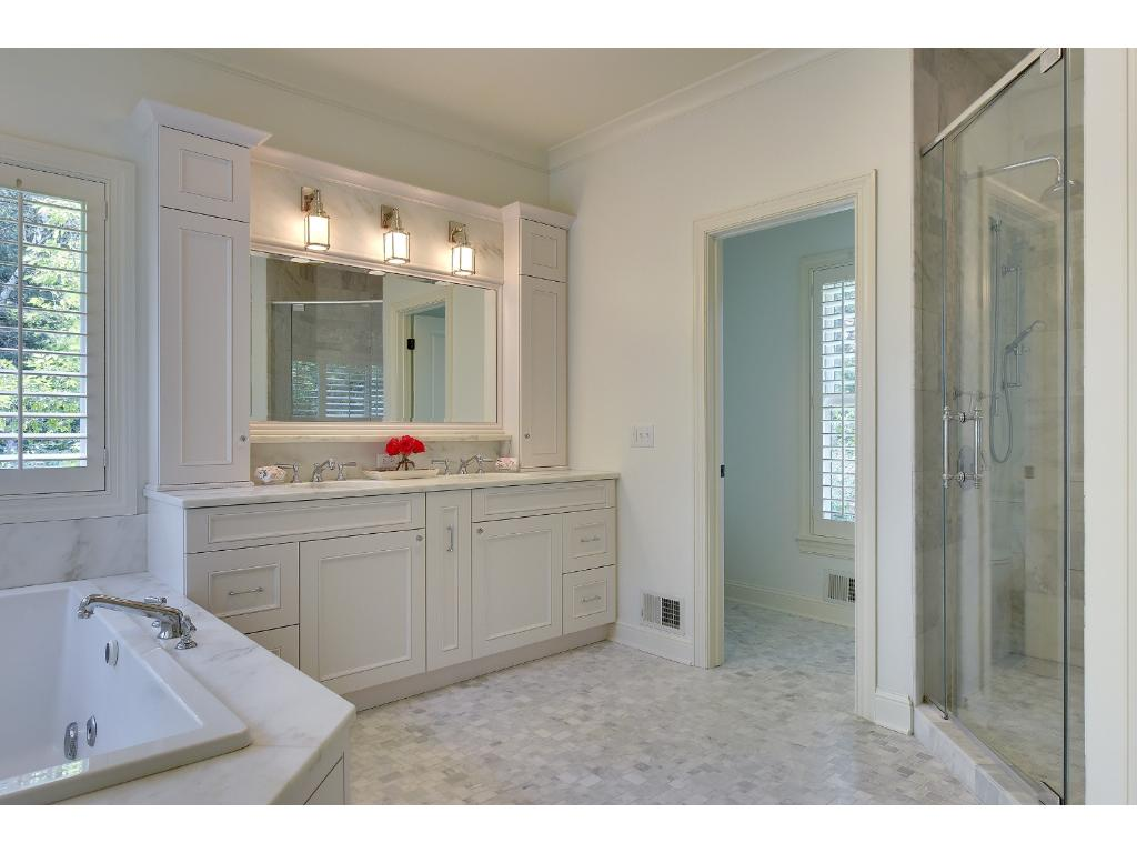 Completely remodeled in 2012 this bathroom features spa finishes, including an elevated marble vanity, marble tiled shower with rain shower head, jacuzzi tub and built-in cabinets with glass fronts.