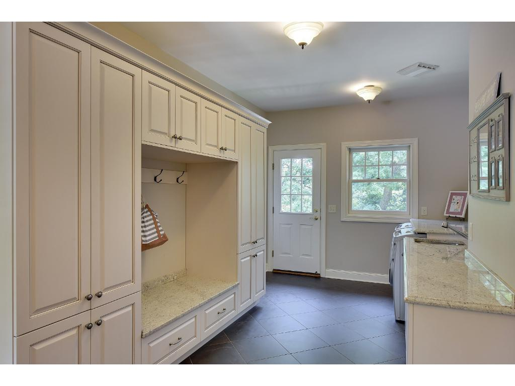 Remodeled in 2009, this spacious Mud Room has access to the deck and backyard. Well equipped with tiled floors, built-in lockers and storage, granite countertops with stainless steel under-mount laundry sink and a Bosch Washing Machine and Dryer.