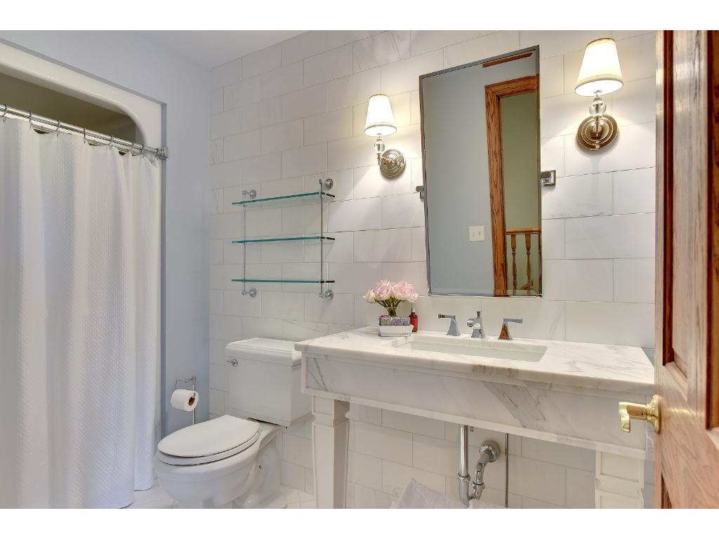 Tucked away on the second floor, you'll find the perfect Man Cave, Nanny/MIL Suite or Guest Quarters. Fitted with a Library, Guest Bedroom and freshly remodeled Bathroom featuring marble subway tile, a marble topped vanity & tiled shower.