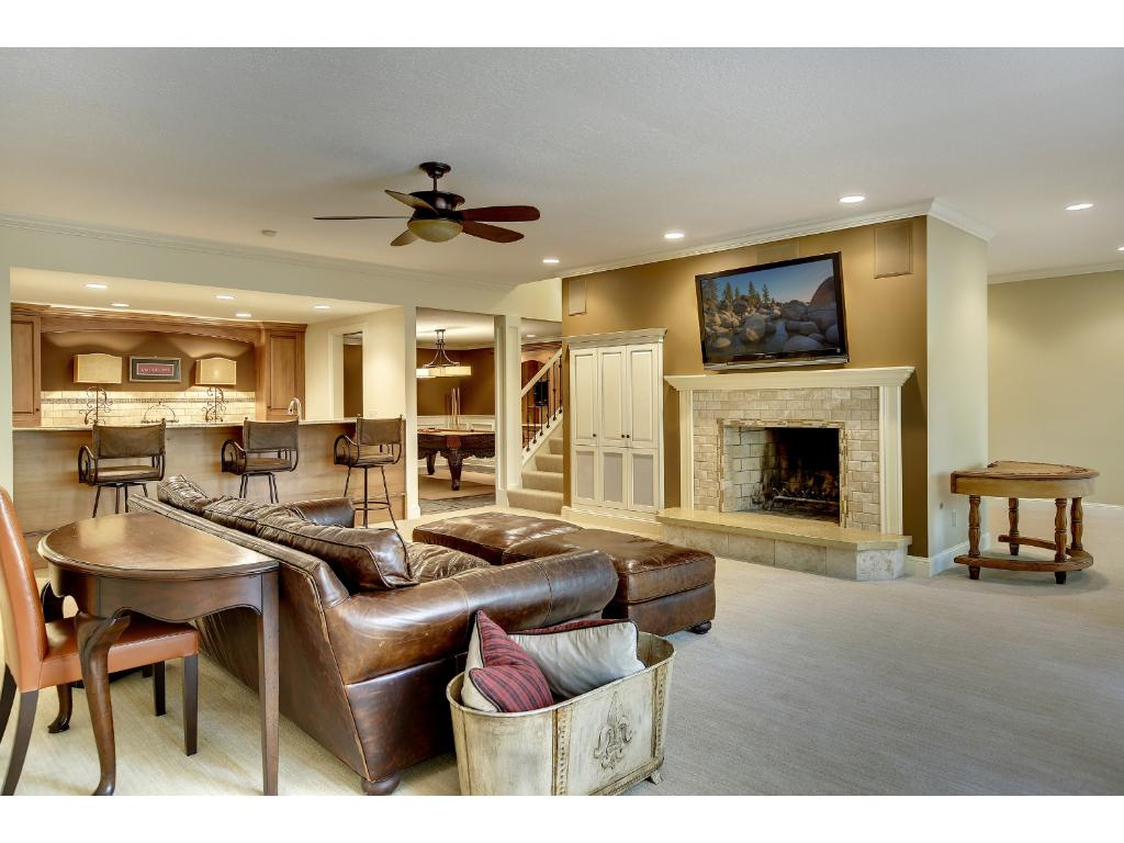 The Lower Level is perfect for entertaining with a spacious Family Room with wood burning Fireplace and travertine tiled surround and oversize windows that look into the private backyard. New carpet was installed in June 2015.