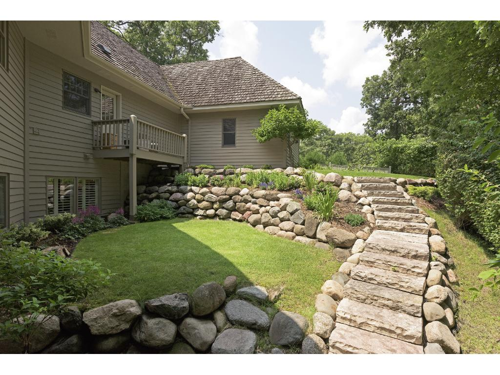 The gardens and grounds that surround the home have been professionally landscaped with boulder walls, walkways and beautiful gardens bring bright colors to the private setting.