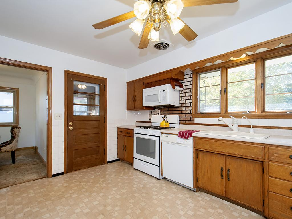 Kitchen opens to sunroom overlooking peaceful back yard.