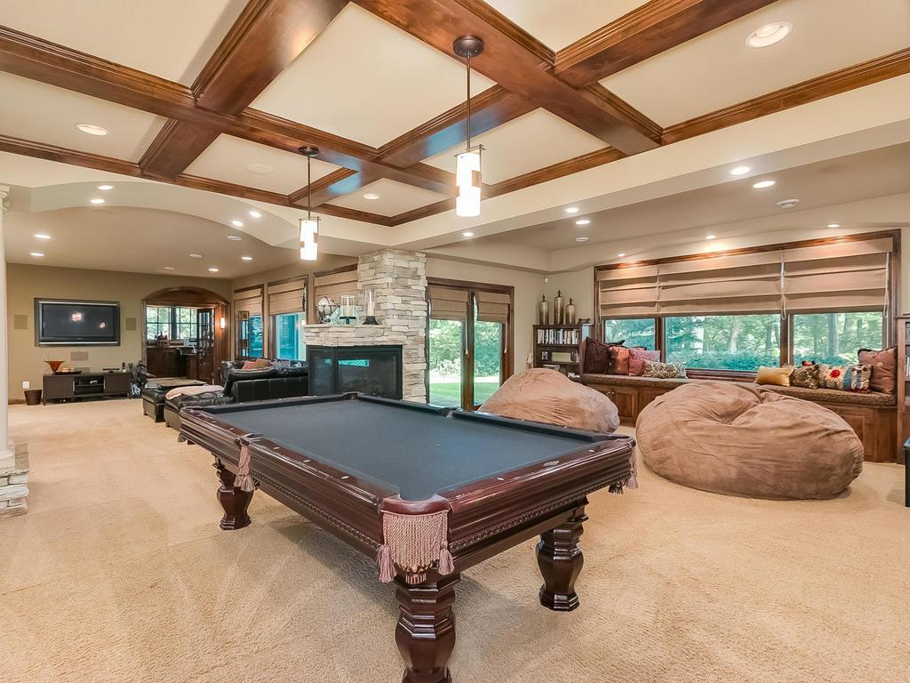 Exceptional walkout lower level has it all. Spacious amusement great room with wet-bar, two-sided fireplace, heated floors, billiards area, theater rm, exercise rm, office/study, hobby rm, 3/4 bath, large storage room, & service door to pool/garage.