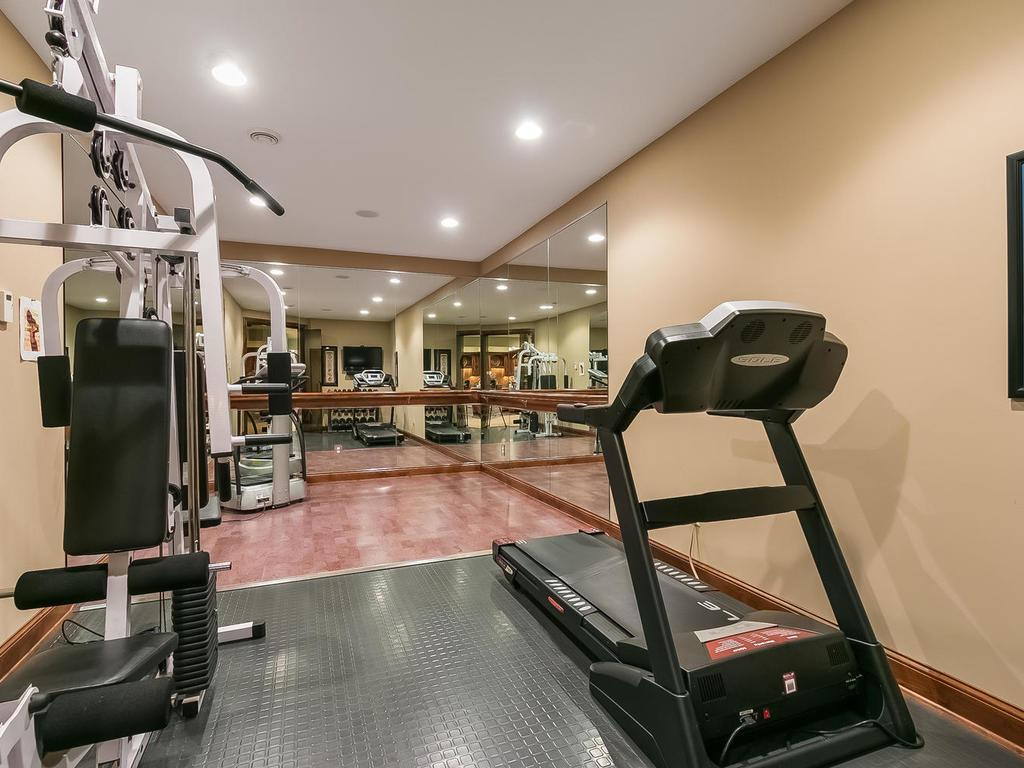 Exercise room with two mirrored walls, recessed lighting and space for equipment.