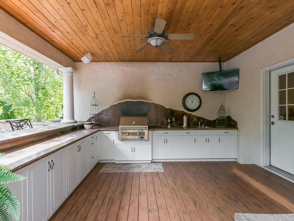 Outdoor kitchenette with built-in stone surround seating, Trex deck, grill station, ample countertop and cabinet space for entertaining, sink and convenient access to indoor 1/2 bath.