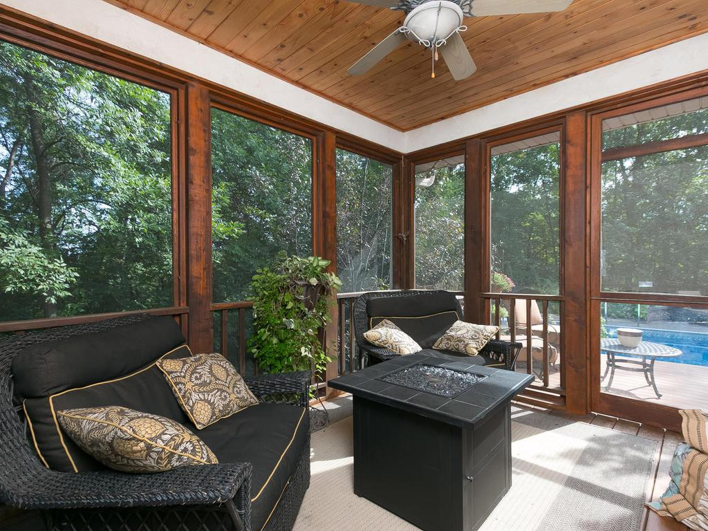 Cozy three season screen porch with dark stain, knotty wood ceiling and ceiling fan, overlooking the picturesque built-in pool.