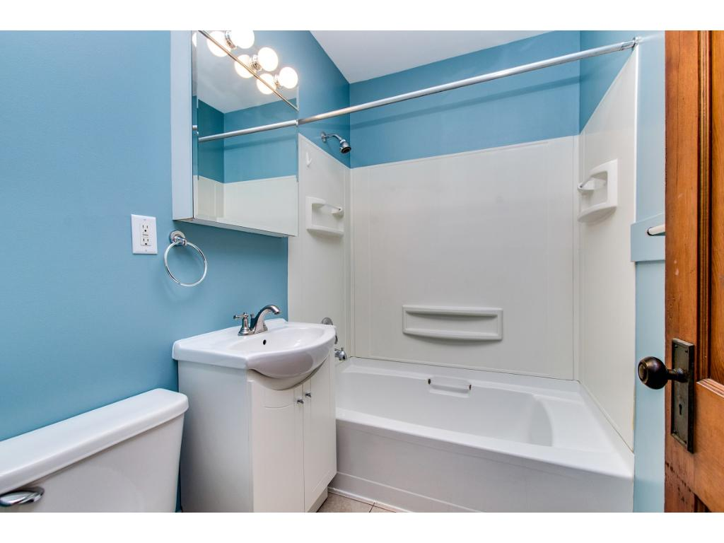Updated bathroom with new vanity, wall cabinet and light fixture. Pre-fab surround and ceramic tile floor for durability and easy maintenance!