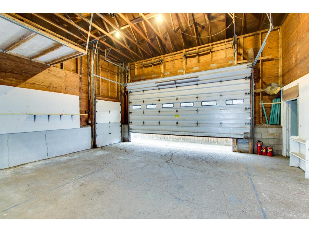 Lots of space! This large garage door opens to daycare next door so new owner may want to move it to north side of room or use the garage doors already on the north side of the building.