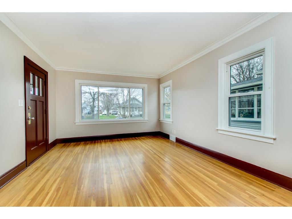 Sun-soaked living room with beautiful hardwood floors! Entire interior has been repainted and looks amazing!