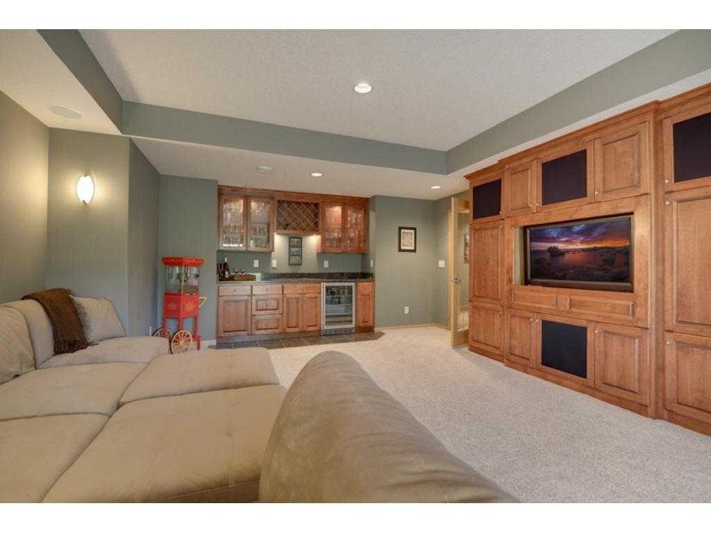 Fabulous, lower level living spaces!  No expense was spared in the custom built-ins including a bar & double-sided Stone fireplace in the family room!