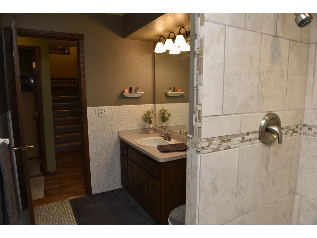 Updated tile surround, new fixtures, and a great blend of colors and textures for a wonderful modern bath.