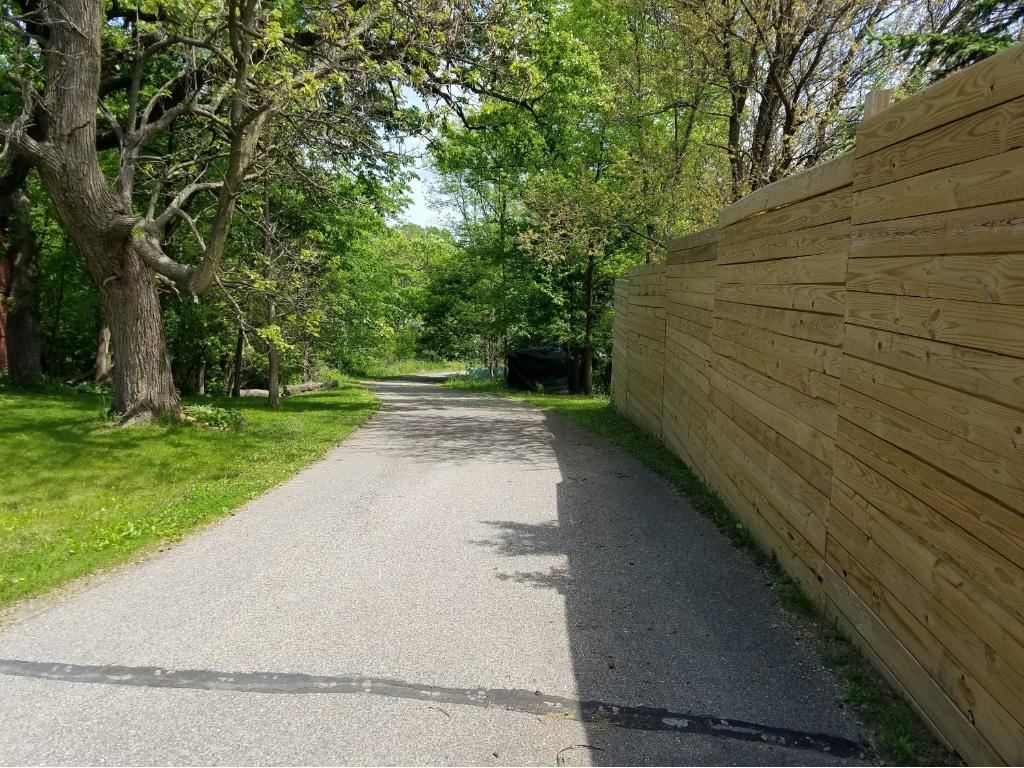 Privacy fence along highway side of driveway